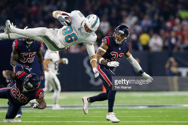 Mike Gesicki of the Miami Dolphins is tackled by Kareem Jackson of the Houston Texans in the second quarter at NRG Stadium on October 25, 2018 in...