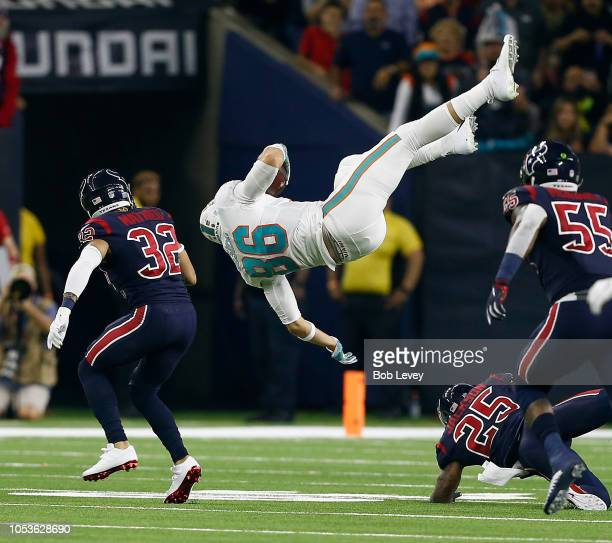Mike Gesicki of the Miami Dolphins is tripped up by Kareem Jackson of the Houston Texans after making a catch and run as Tyrann Mathieu and...
