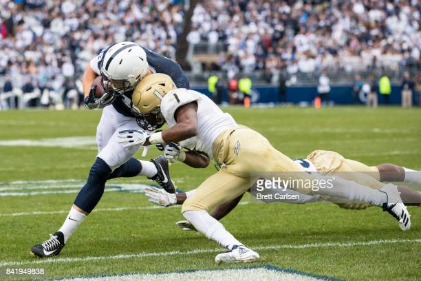 Mike Gesicki of the Penn State Nittany Lions collides with Alvin Davis of the Akron Zips at the goal line during a touchdown reception in the second...