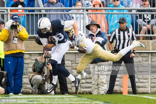 Mike Gesicki of the Penn State Nittany Lions hangs on to a touchdown reception as James King of the Akron Zips attempts to tackle at 049 in the first...