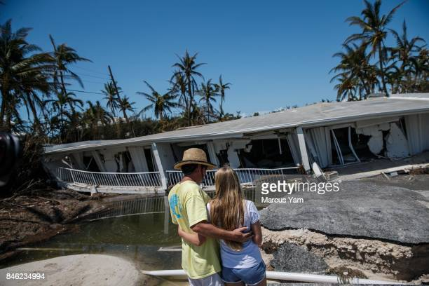 Mike Gilbert and his daughter Brooke Gilbert embrace each other as they stand in front of a family member's destroyed condominium building in the...