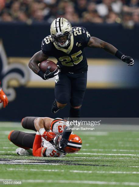 Mike Gillislee of the New Orleans Saints runs the ball as Joe Schobert of the Cleveland Browns attempts to tackle him during the second quarter...