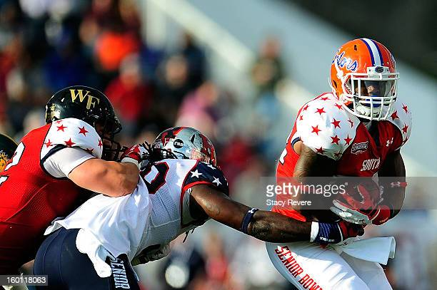 Mike Gillislee of the South squad is pursued by Khaseem Greene of the North squad during the first half of the Senior Bowl at Ladd Peebles Stadium on...