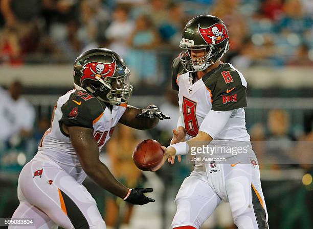 Mike Glennon hands the ball off to Peyton Barber of the Tampa Bay Buccaneers against the Jacksonville Jaguars during a preseason game on August 20...