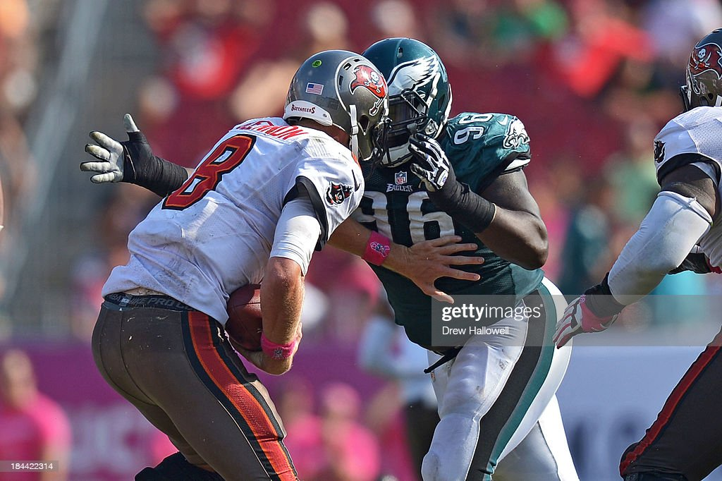 Mike Glennon #8 of the Tampa Bay Buccaneers is sacked by Bennie Logan #96 of the Philadelphia Eagles at Raymond James Stadium on October 13, 2013 in Tampa, Florida. The Eagles won 30-21.