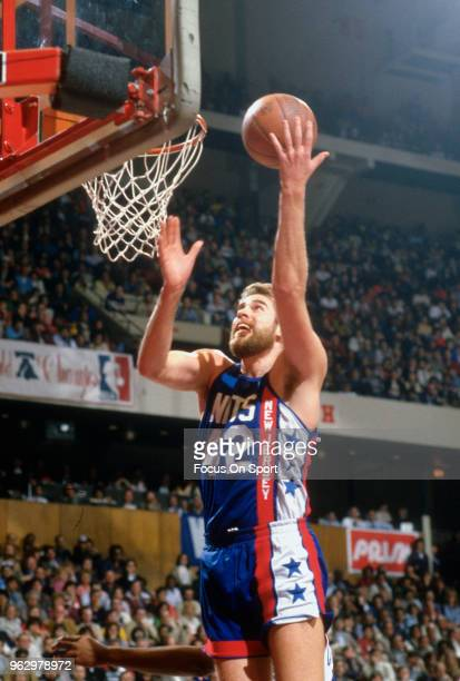 Mike Gminski of the New Jersey Nets goes in for a layup against the Philadelphia 76ers during an NBA basketball game circa 1984 at The Spectrum in...