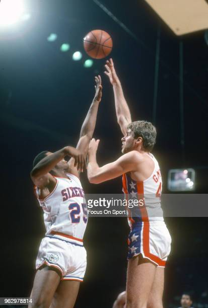 Mike Gminski of the New Jersey Nets shoots over Earl Cureton of the Philadelphia 76ers during an NBA basketball game circa 1981 at The Spectrum in...