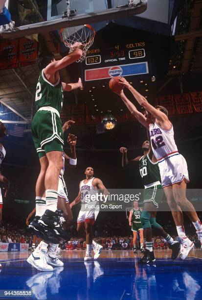 Mike Gminski of the Philadelphia 76ers grabs a rebound over Robert Parish and Kevin McHale of the Boston Celtics during an NBA basketball game circa...
