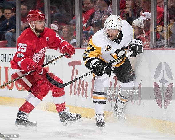 Mike Green of the Detroit Red Wings battles along the boards with Bryan Rust of the Pittsburgh Penguins during an NHL game at Joe Louis Arena on...