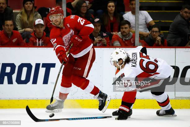 Mike Green of the Detroit Red Wings passes the puck over the stick of Erik Karlsson of the Ottawa Senators during the third period at Joe Louis Arena...