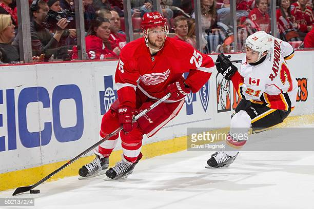 Mike Green of the Detroit Red Wings skates around the net with the puck in front of Mason Raymond of the Calgary Flames during an NHL game at Joe...