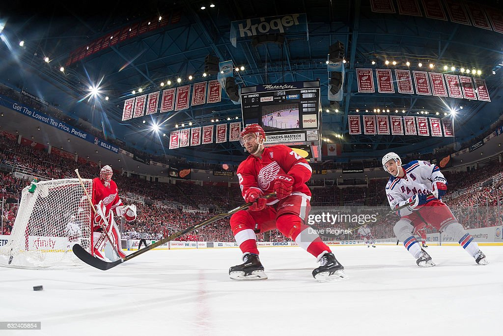 Mike Green #25 of the Detroit Red Wings skates with the puck behind the net followed by Derek Stepan #21 of the New York Rangers during an NHL game at Joe Louis Arena on January 22, 2017 in Detroit, Michigan. The Rangers defeated the Wings 1-0 in overtime.