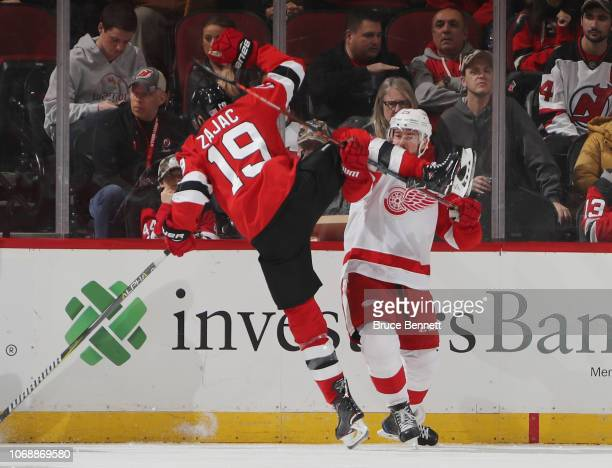 Mike Green of the Detroit Red Wings upends Travis Zajac of the New Jersey Devils during the first period at the Prudential Center on November 17,...