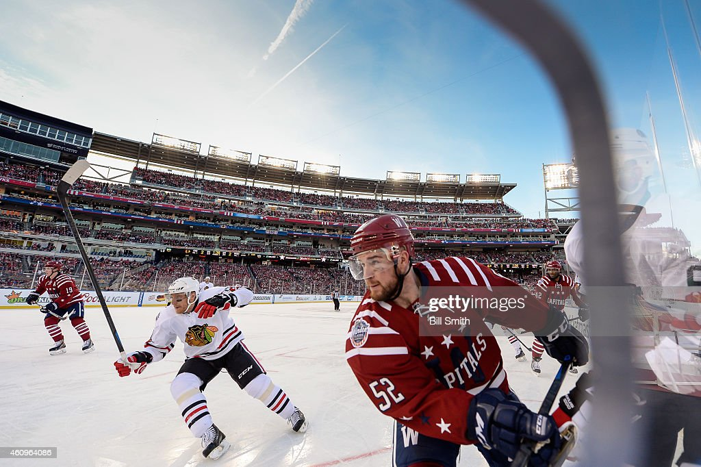 Mike Green #52 of the Washington Capitals and Marian Hossa #81 of the Chicago Blackhawks skate around the boards during the 2015 Bridgestone NHL Winter Classic on January 1, 2015 in Washington, DC.
