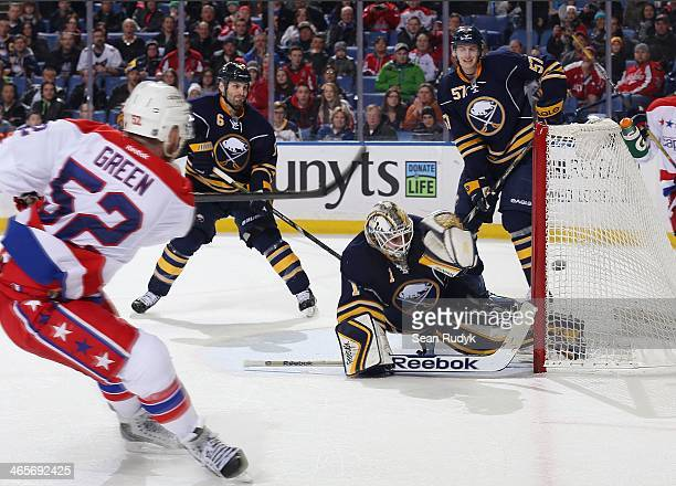 Mike Green of the Washington Capitals scores the gamewinning overtime goal against Jhonas Enroth of the Buffalo Sabres on January 28 2014 at the...
