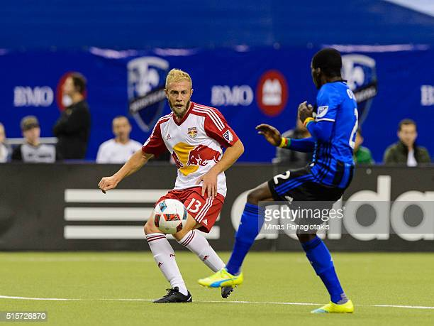 Mike Grella of the New York Red Bulls plays the ball near Ambroise Oyongo of the Montreal Impact during the MLS game at the Olympic Stadium on March...