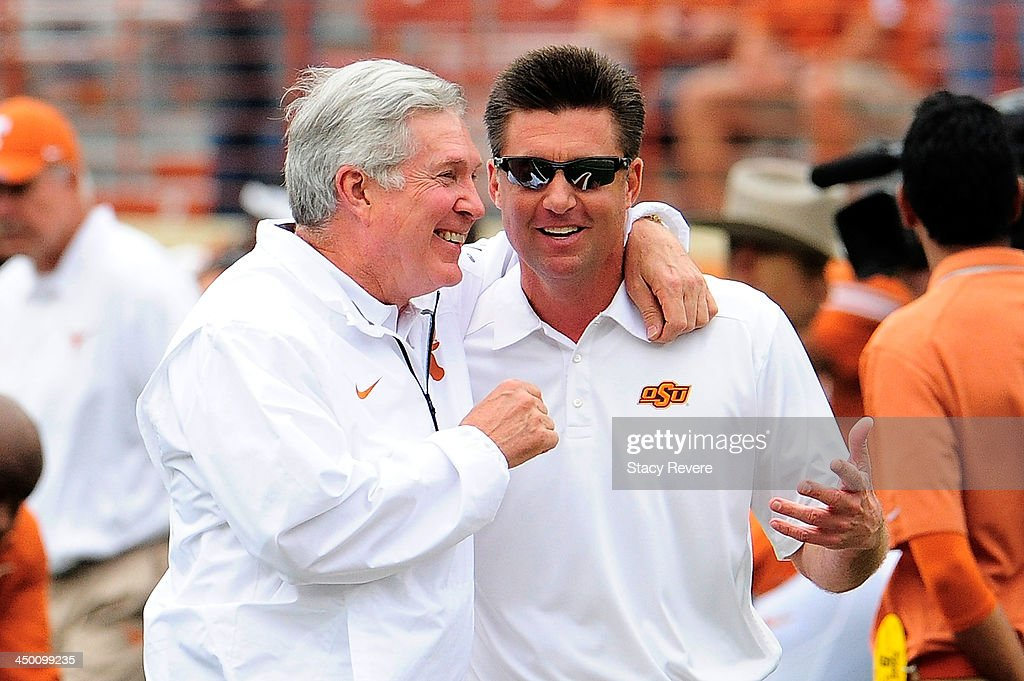 Mike gundy, head coach of the Oklahoma State Cowboys, and Mack Brown, head coach the Texas Longhorns, meet at midfield prior to a game at Darrell K Royal-Texas Memorial Stadium on November 16, 2013 in Austin, Texas. Oklahoma State won the game 38-13.