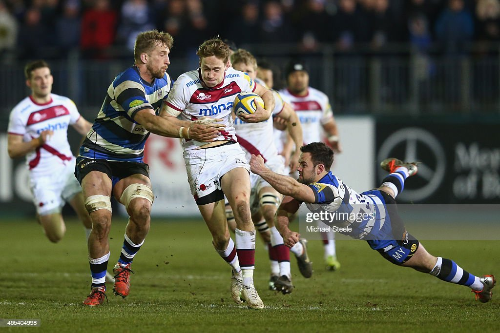 Mike Haley (C) of Sale bursts between Dominic Day (L) and Micky Young (R) of Bath during the Aviva Premiership match between Bath Rugby and Sale at the Recreation Ground on March 6, 2015 in Bath, England.