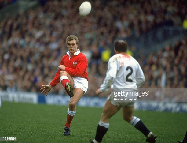 Mike Hall of Wales kicks the ball over Brian Moore of England during the Five Nations Championship match between England and Wales at Twickenham in...