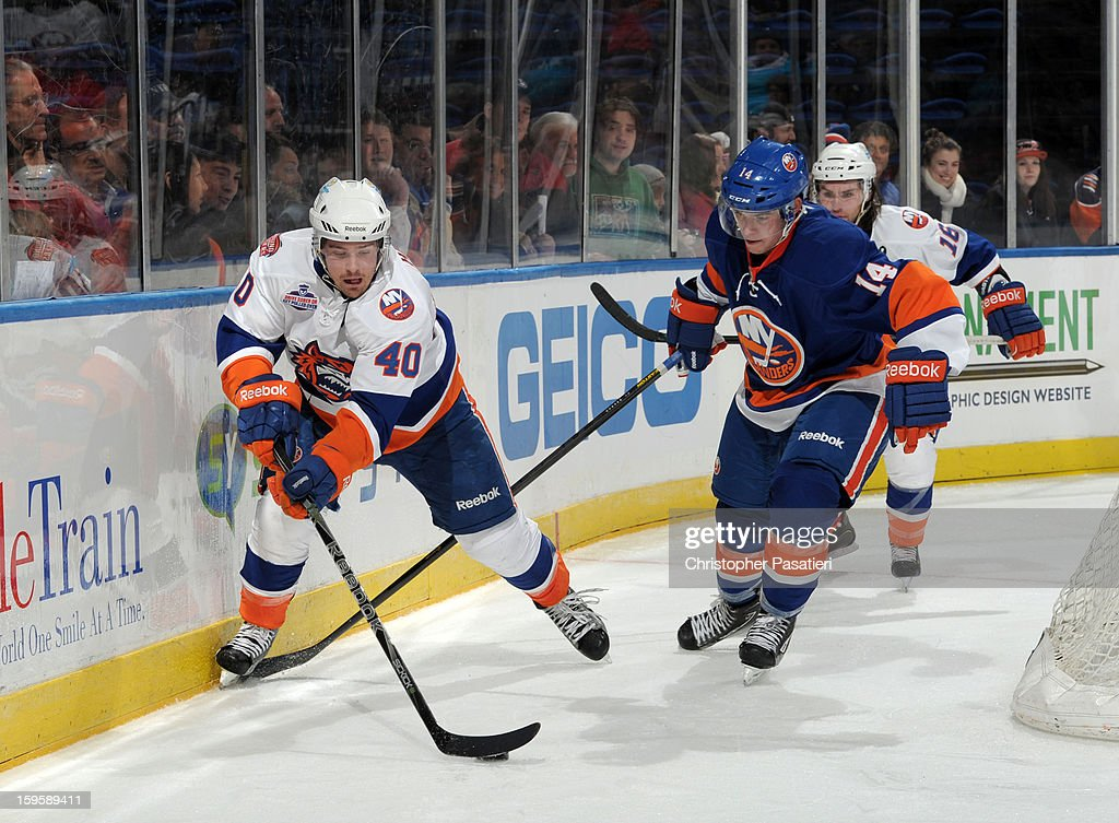 Mike Halmo #40 of Team White reaches for the puck against Thomas Hickey #14 of Team Blue during a scrimmage match between players of the New York Islanders and Bridgeport Sound Tigers on January 16, 2013 at Nassau Veterans Memorial Coliseum in Uniondale, New York.