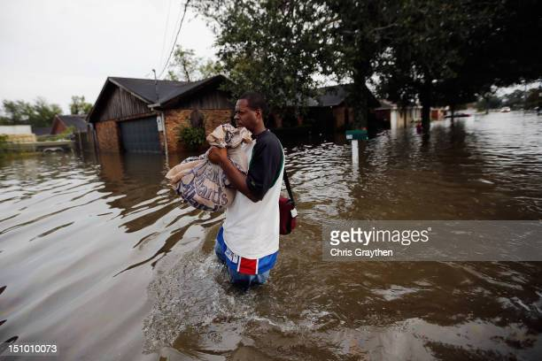 Mike Hamilton walks through waters from Hurricane Isaac on August 30 2012 in Reserve Louisiana Isaac downgraded Wednesday to a tropical depression is...