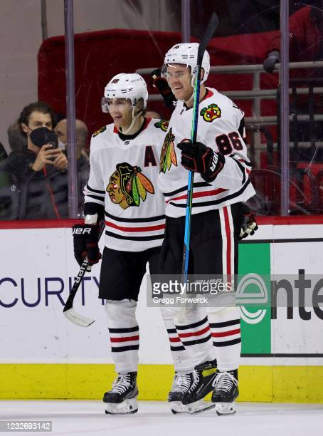 Mike Hardman of the Chicago Blackhawks scores a goal and celebrates with teammate Patrick Kane during an NHL game against the Carolina Hurricanes on...