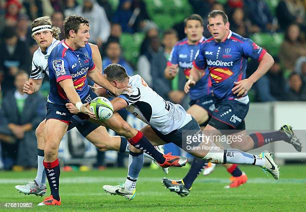 Mike Harris of the Rebels passes the ball whilst being tackled by Alby Mathewson of the Force defence during the round 18 Super Rugby match between...
