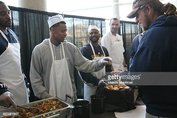 Mike Harris Trey Burke John Lucas III and Michael Sanders Assistant Coach of the Utah Jazz dish out food during the we carewe share Thanksgiving...