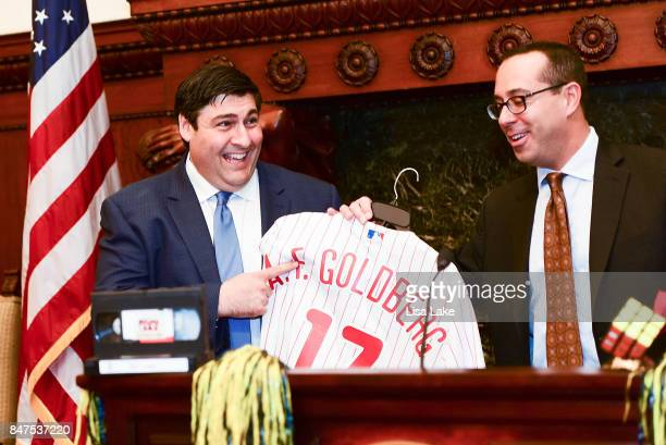 Mike Harris VP Marketing New Media presents Producer Adam F Goldberg with customized official Philadelphia Phillies shirt and cap during an event...