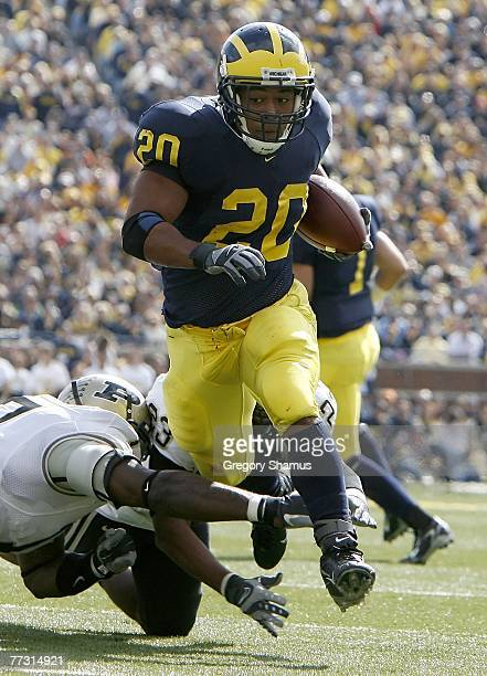 Mike Hart of the Michigan Wolverines races past Josh Ferguson and and Justin Scott of the Purdue Boilermakers for a second quarter touchdown on...