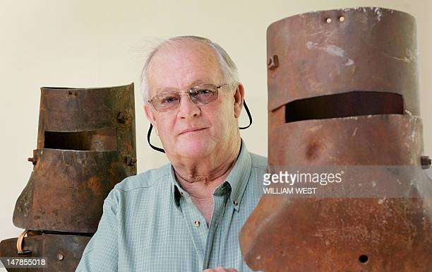 Mike Hastings poses between the helmets of famous Australian outlaw Ned Kelly in his home town of Jerilderie some 750 kilometres southwest of Sydney...