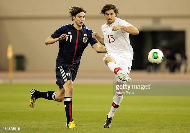 Mike Havenaar of Japan challenges Dejan Jakovic of Canada during the international friendly match between Japan and Canada at Khalifa International...