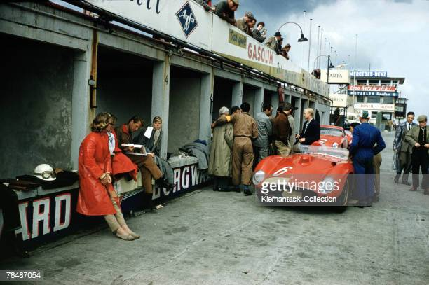 Mike Hawthorn standing next to his car in conversation with team manager Romulo Tavoni and others in the Ferrari pits during practice at the...