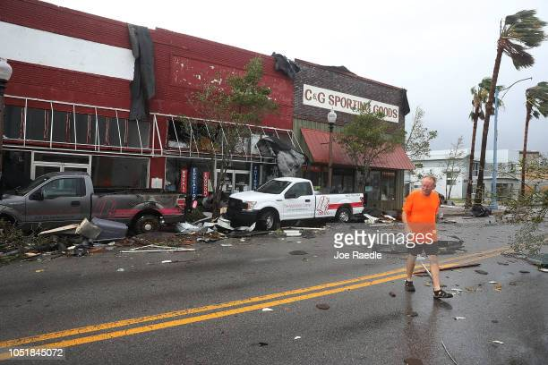 Mike Hays walks past damaged stores after hurricane Michael passed through the downtown area on October 10 2018 in Panama City Florida The hurricane...