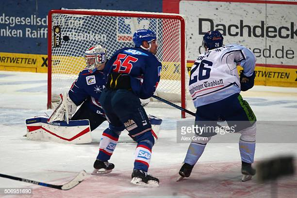 Mike Hedden of Straubing scores his team's third goal against goalkeeper Youri Ziffzer and Jochen Hecht of Mannheim during the DEL match between...