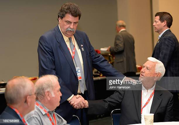 Mike Helton President of NASCAR greets Junior Johnson during the Hall of Fame Selection at NASCAR Hall of Fame on May 22 2013 in Charlotte North...