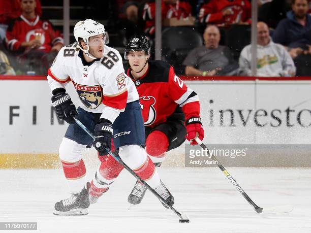 Mike Hoffman of the Florida Panthers skates with the puck against Damon Severson of the New Jersey Devils during the first period on October 14 2019...