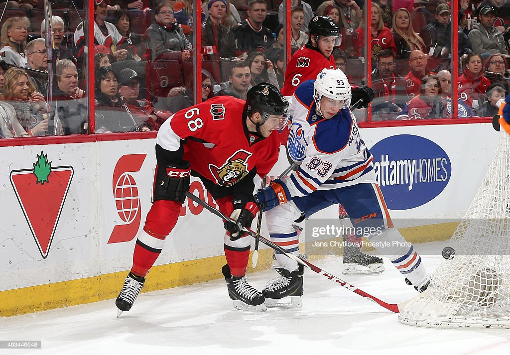 Mike Hoffman #68 of the Ottawa Senators battles for the puck against Ryan Nugent-Hopkins #93 of the Edmonton Oilers in the second period at Canadian Tire Centre on February 14, 2015 in Ottawa, Ontario, Canada.
