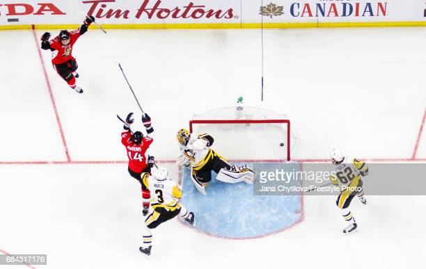 Mike Hoffman of the Ottawa Senators celebrates his first period goal with teammate Alexandre Burrows as MarcAndre Fleury Olli Maatta and Carl Hagelin...