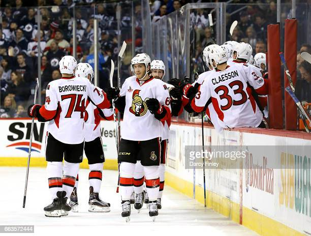 Mike Hoffman of the Ottawa Senators celebrates his second period goal against the Winnipeg Jets with teammates at the bench at the MTS Centre on...