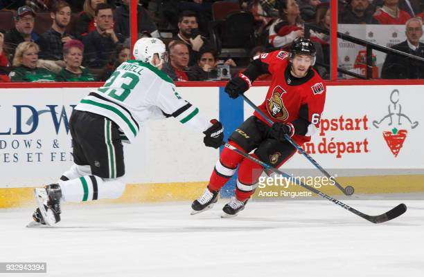 Mike Hoffman of the Ottawa Senators chips the puck past Esa Lindell of the Dallas Stars at Canadian Tire Centre on March 16 2018 in Ottawa Ontario...