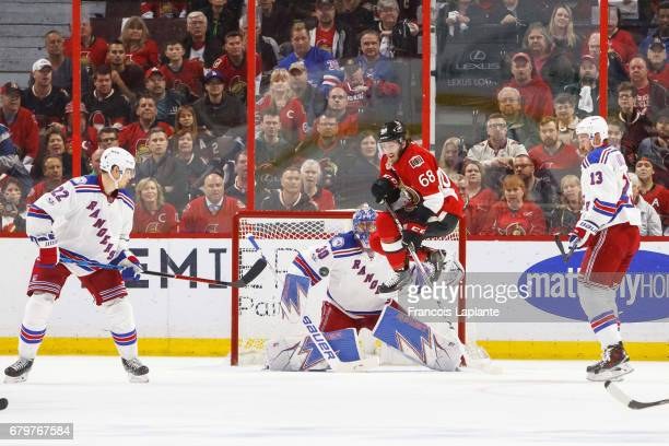 Mike Hoffman of the Ottawa Senators jumps as in inbound shot if fired against Henrik Lundqvist of the New York Rangers as Nick Holden and Kevin Hayes...