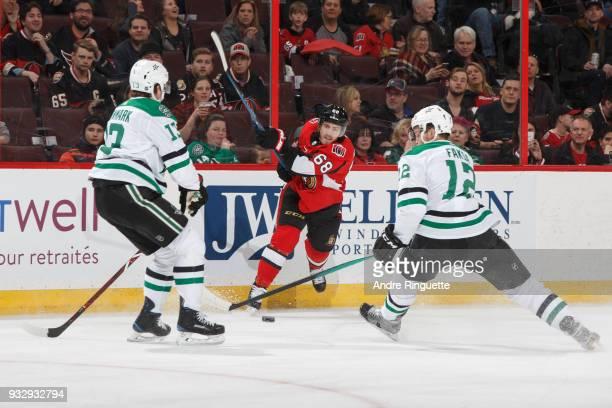 Mike Hoffman of the Ottawa Senators shoots the puck as Mattias Janmark and Radek Faksa of the Dallas Stars attempt to block the shot at Canadian Tire...