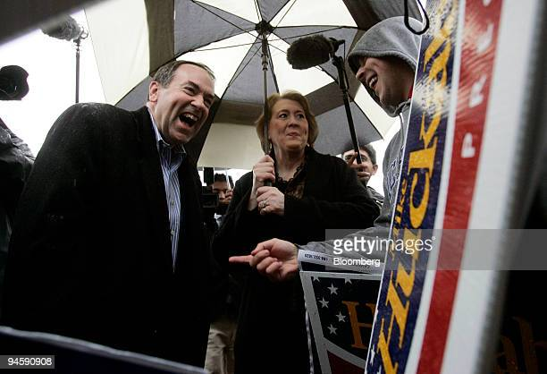Mike Huckabee former governor of Arkansas and 2008 Republican presidential candidate left and his wife Janet Huckabee right greet a supporter at a...