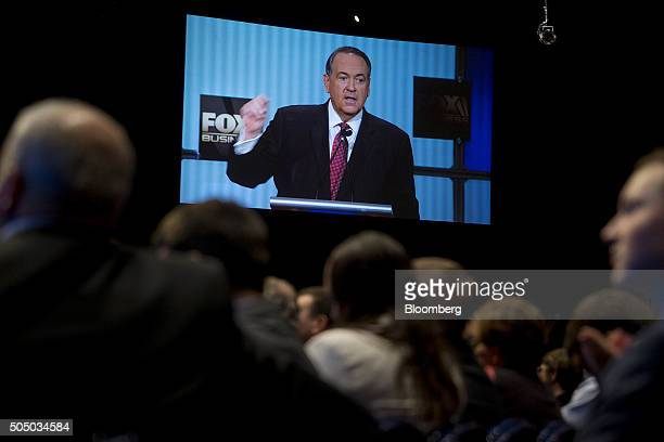 Mike Huckabee former governor of Arkansas and 2016 Republican presidential candidate is seen on a television screen as he speaks during the...