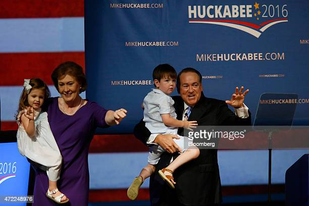 Mike Huckabee former governor of Arkansas right and his wife Janet Huckabee hold two of their grandchildren during his announcement that he will seek...