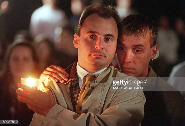 Mike Hughes and Richard Carr embrace each other as they participate in a vigil at the Capitol in Washington DC 14 October to honor the life of...