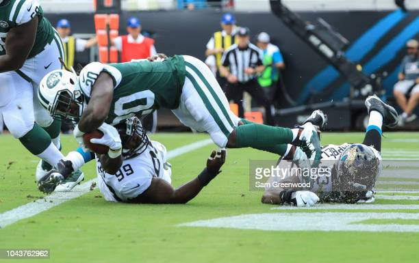 Mike Hughes Jr #99 of the Jacksonville Jaguars and Calais Campbell of the Jacksonville Jaguars tackle Isaiah Crowell of the New York Jets for a...