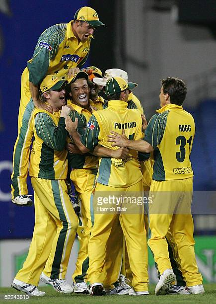 Mike Hussey of Australia comes over the top of his team's celebration of the run out of Hamish Marshall of New Zealand during the 3rd One Day...