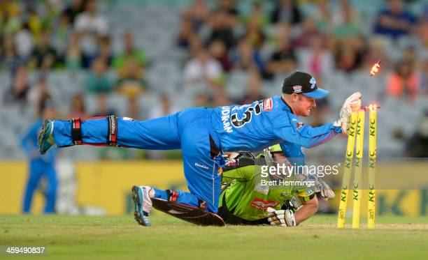 Mike Hussey of the Thunder dives into his crease to avoid being run out by Tim Ludeman of the Strikers during the Big Bash League match between...
